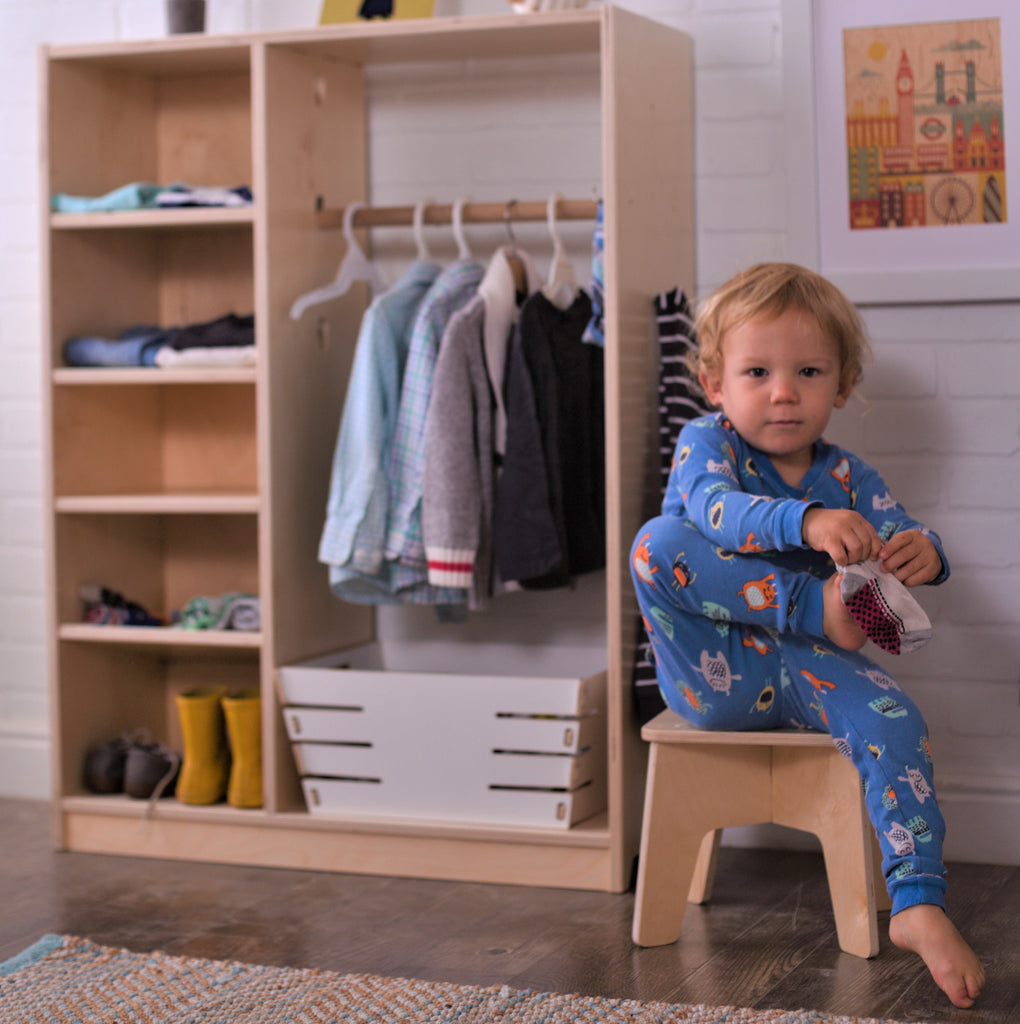 Montessori Children's Wardrobe filled with children's clothes and child putting on socks seated on a Stubby Stool.