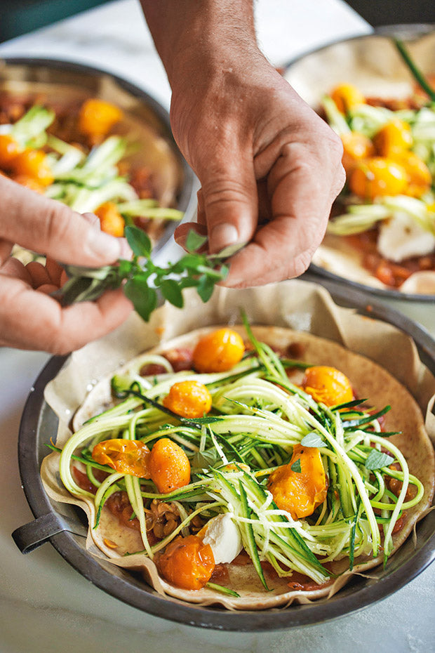 This fresh, homemade pizza is topped with courgette noodles, rocket and soft goat cheese.