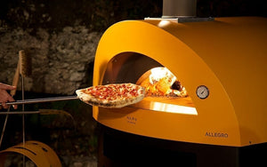 Great Outdoor Pizza Ovens pizza inserted into yellow Alfa Allegro outdoor wood-fired pizza oven