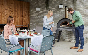 people gathered around Great Outdoor Pizza Ovens gray Alfa Ciao outdoor wood-fired pizza oven
