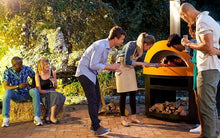 Great Outdoor Pizza Ovens friends gathered around yellow Alfa Allegro outdoor wood-fired pizza oven