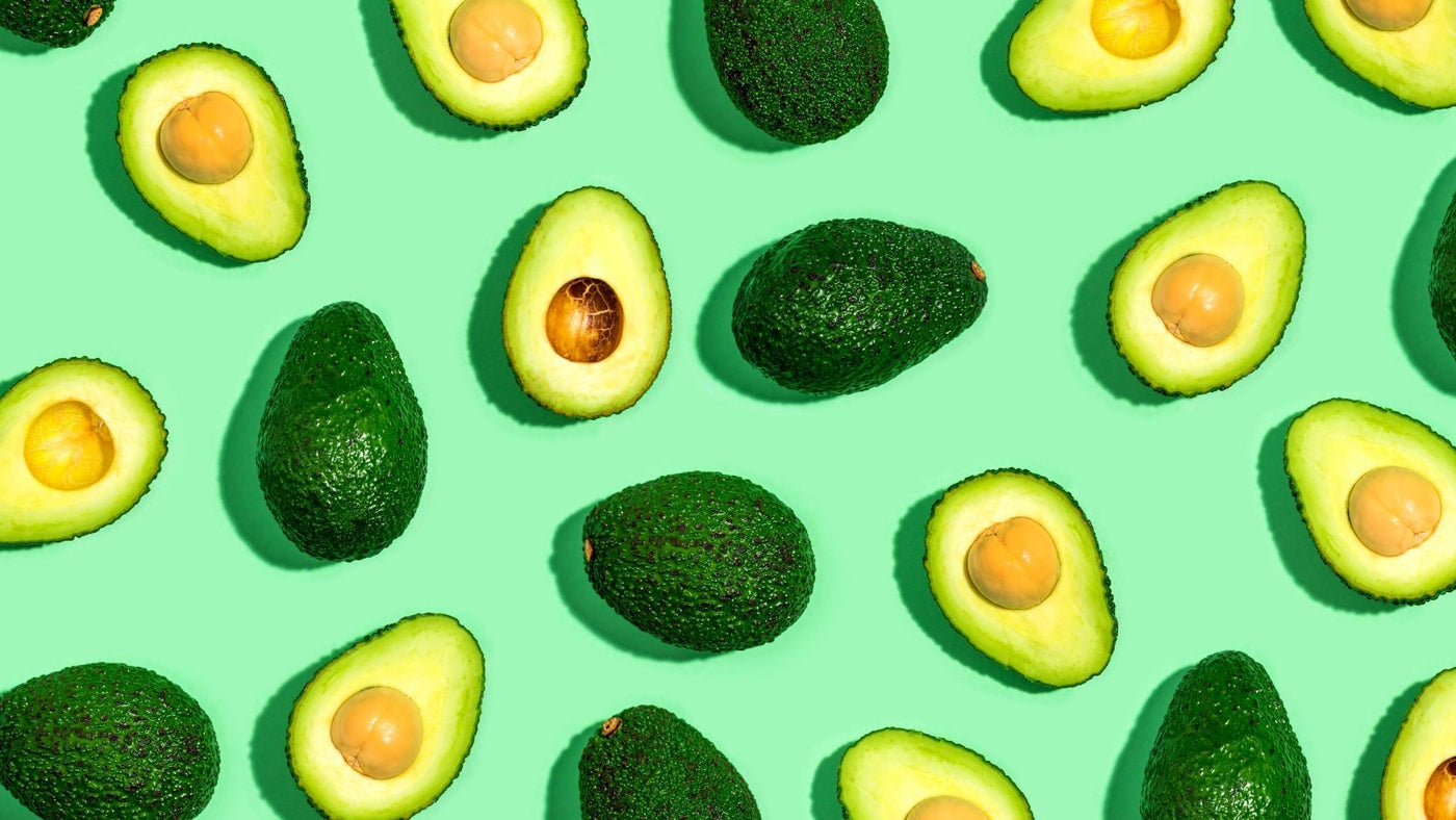 whole and sliced avocados on a green background