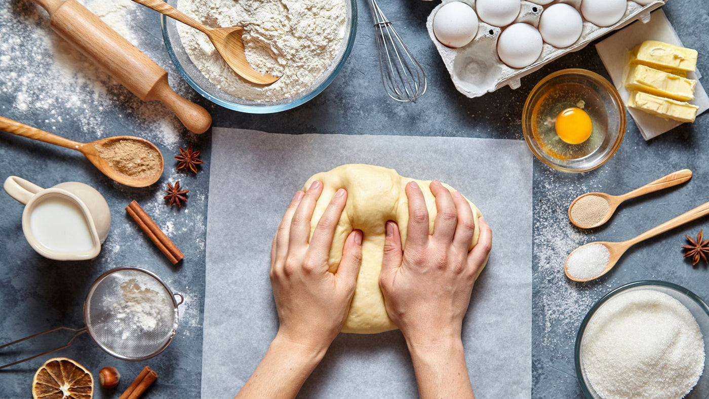 person kneading dough and ingredients for bread