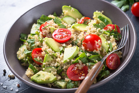 bowl of quinoa salad with spinach and tomatoes
