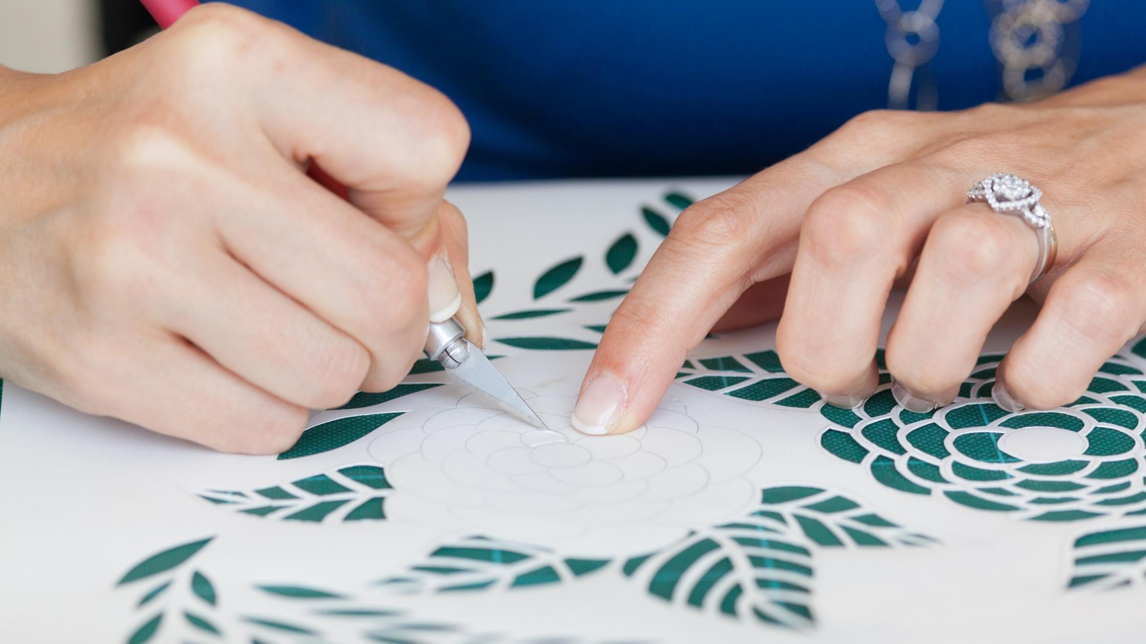 woman cutting a floral design on tracing paper