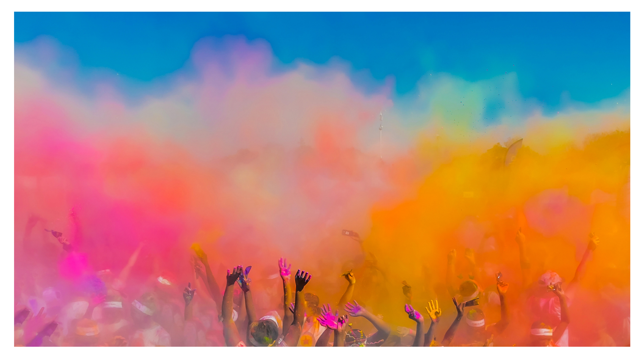 people's hands upraised in front of colored powder dust during holi festival in india
