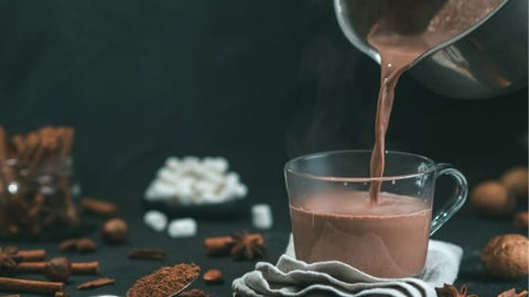 Pouring hot chocolate from a pan to a mug. eat2explore