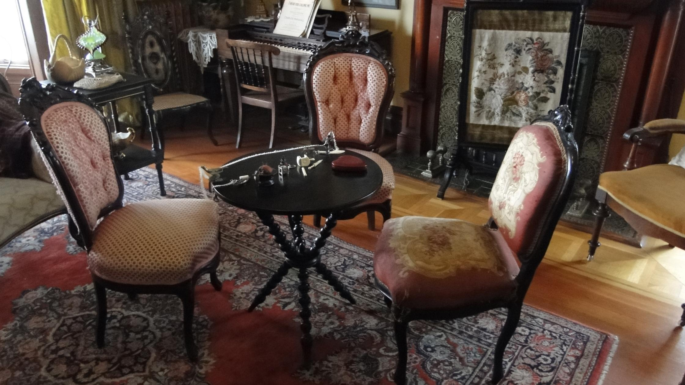 vintage victorian parlor with three chairs and tea table