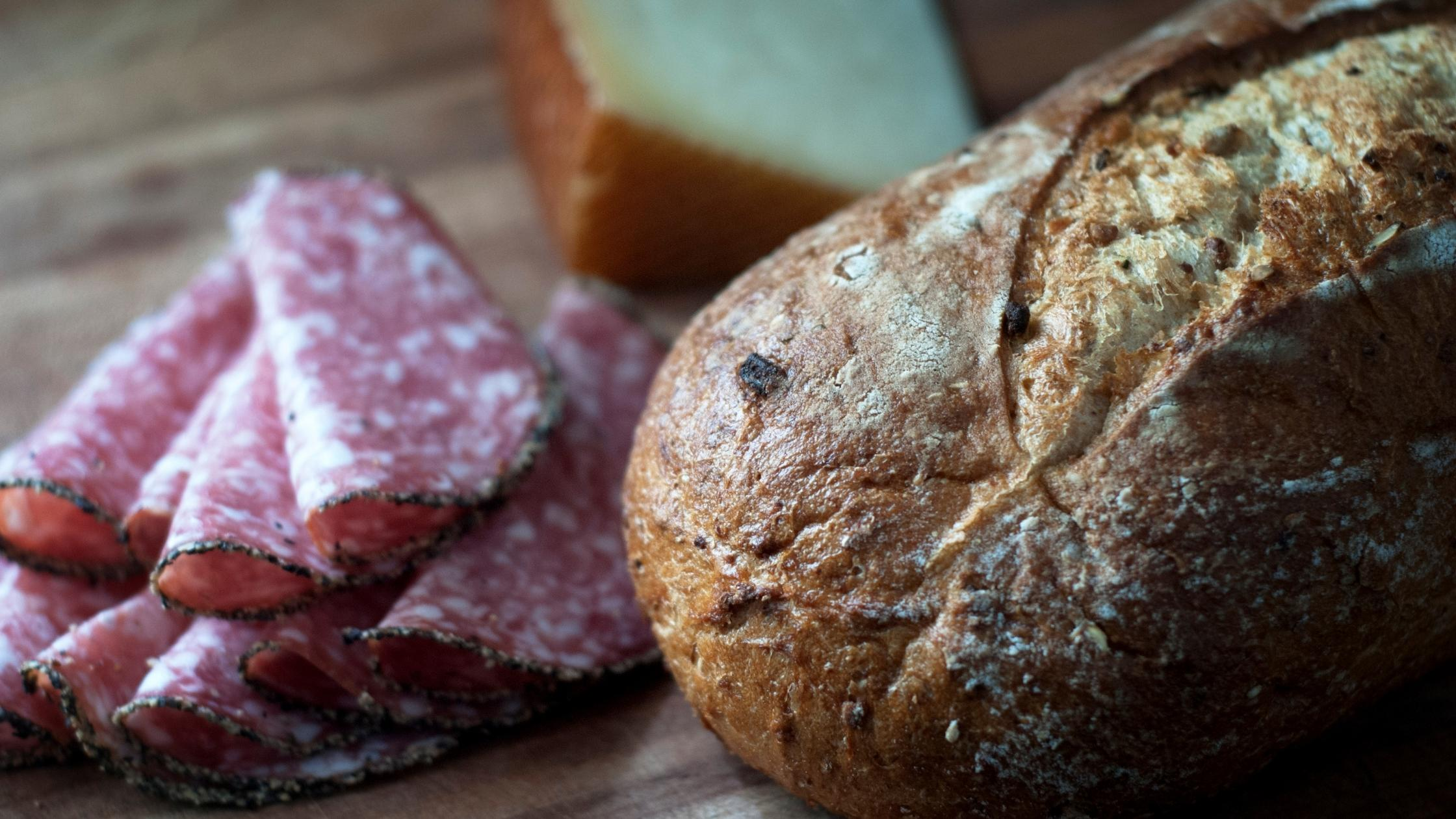 rustic bread, sliced meat and a block of cheese