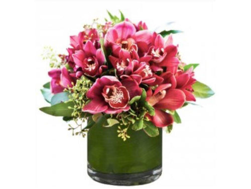 Orchid and greenery arrangement in a vase
