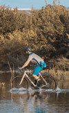 Man riding Obed Boundary gravel bike through water