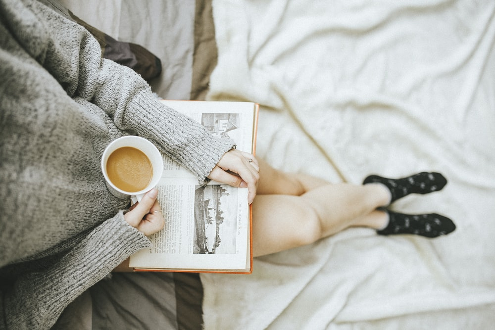 You woman in comfortable clothing, drinking a hot beverage and reading a book.