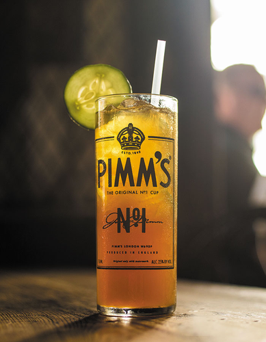 Pimm's Cup shown on table full of famous Pimm's cocktail and a wedge of lime.