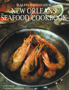 "Book Cover says ""Ralph Brennan's New Orleans Seafood Cookbook"" in white over photo of delicious gulf shrimp cooking in a pot."