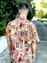 The back side of the shirt, all over printed with abstract patterns. Red and beige are the main colors.