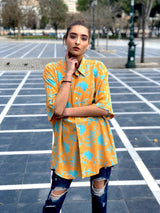 A woman at a square wearing an orange vintage printed shirt from the 90s.