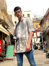 A male model in front of old buildings, wearing a 90s fashion, unique printed vintage shirt.