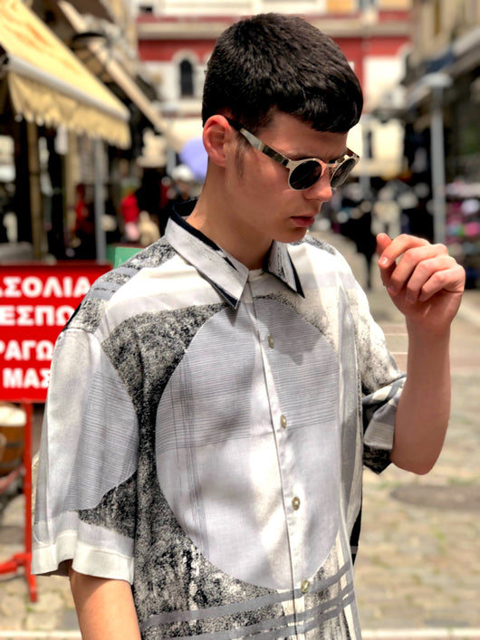 A man wearing a a grey, geometric patterned vintage shirt from the 1990s.