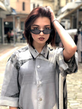 A female model in an urban enviroment, wearing a 90s fashion, unique printed vintage shirt.