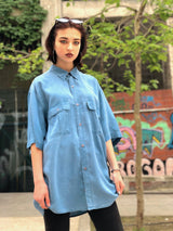 Female model wearing a vintage style shirt with double pockets in an urban background