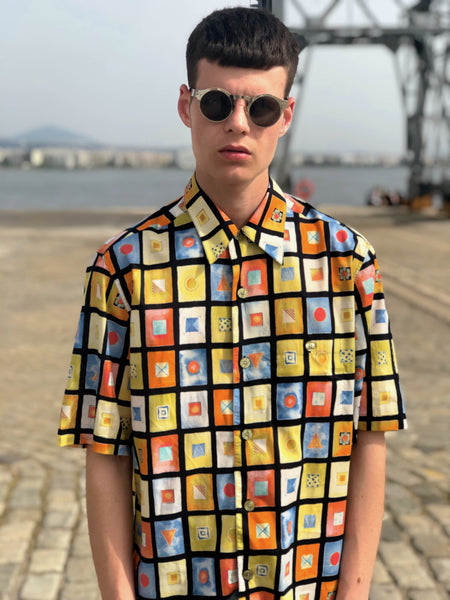 A man with sunglasses at the docks, wearing a multicolor vintage shirt characterized by the 90s fashion aesthetics.