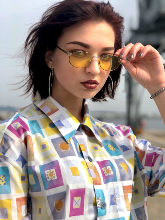 A woman with sunglasses, wearing a multicolor vintage shirt characterized by the 90s fashion aesthetics.
