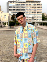 Man wearing an abstract printed shirt with pastel colors in an urban enviroment.