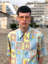 A male model wearing a 1980s geometric shirt of multiple collors and patters.