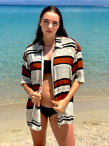 A female model in front of the sea, wearing a zip up vintage shirt from the 1980s with patterns and stripes.