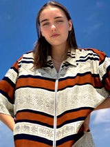 A woman wearing a vintage, 80's fashion shirt with patterns and multicolor stripes.