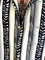 Close up on the black and white stripes and the buttons of the shirt.