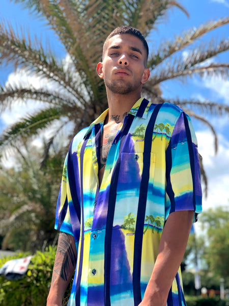 Man wearing a 90's Hawaiian Printed Vintage Shirt in front of a palm tree.