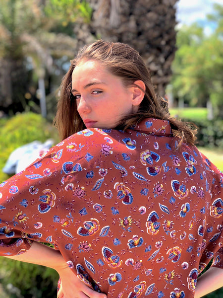 A woman looking over her back, wearing a multicolor printed shirt from the 80s era.
