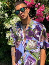 A man wearing a multicolor printed hawaiian vintage shirt from the 90's. Purple is the main color of the clothing item. The background is consisted of flowers.