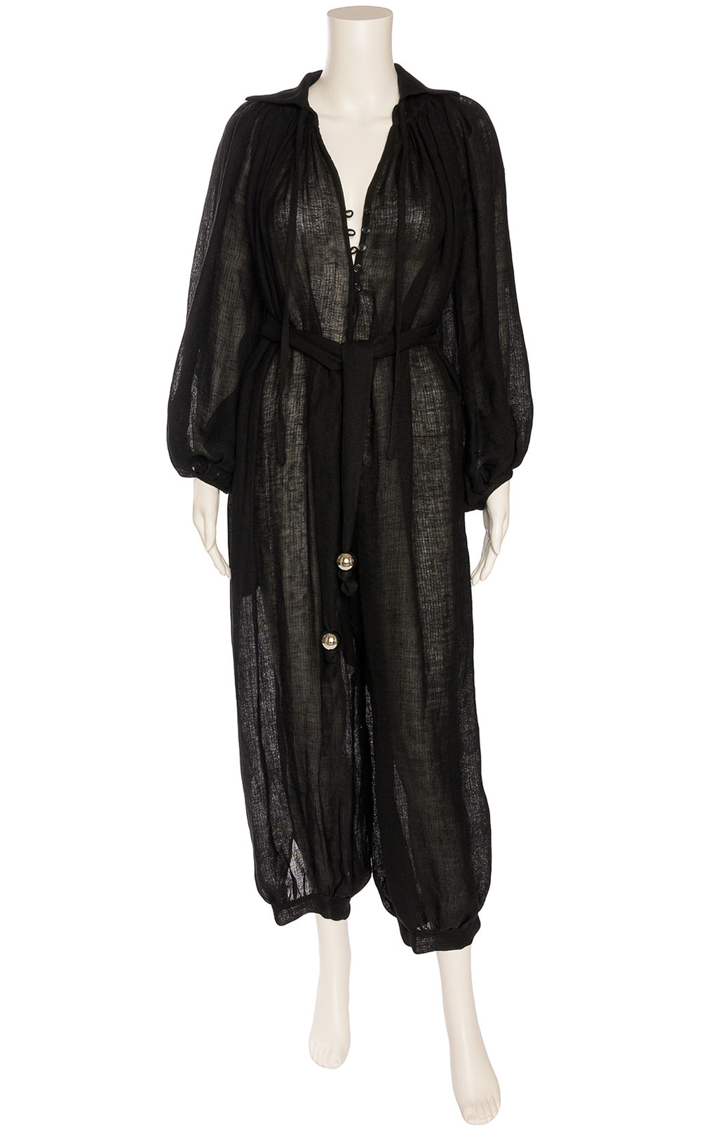 Black full volume jumpsuit with front button closure, collar, full sleeves, side pockets and harem pant bottom with matching belt and gold ball decoration