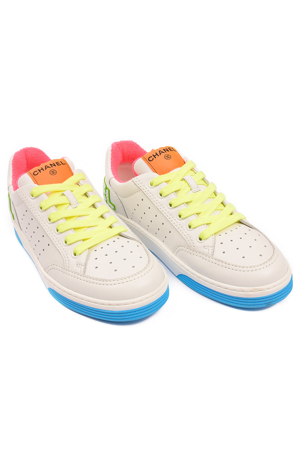 White leather lace up tennis shoe with yellow laces, orange pink green and blue accent colors