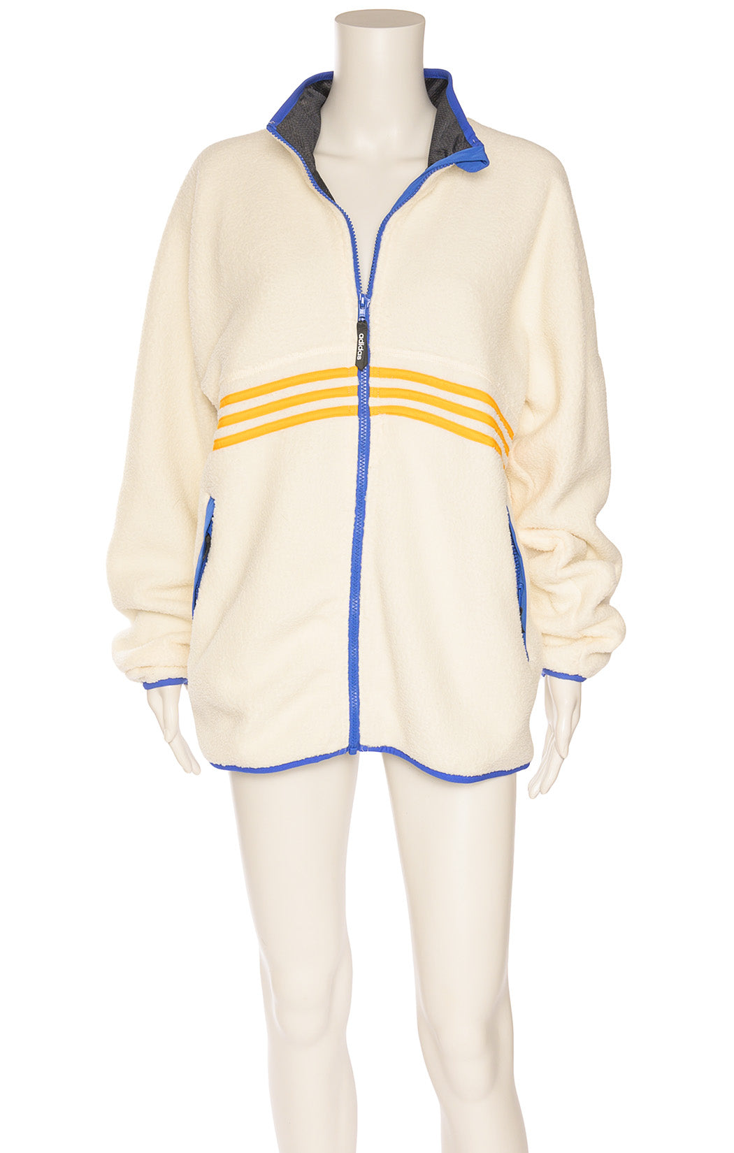 Ivory colored with yellow and blue stripes polar jacket with zipper front closure and front zippered pockets