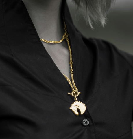 Model wearing a solid 9ct gold Farah horsehead necklace on model next to horse