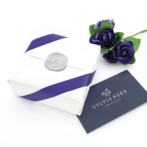 Giftwrapped parcel with crisp white pinstripe wrapping paper with luxury purple ribbon and wax seal