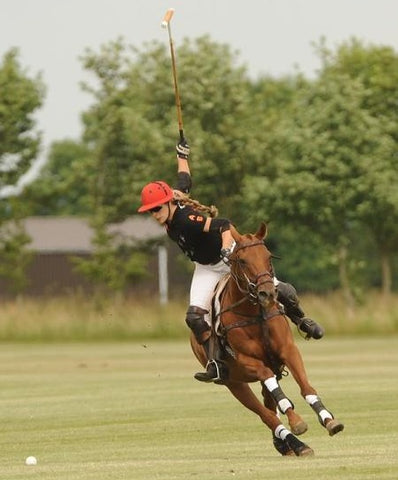 girl playing polo on bay horse