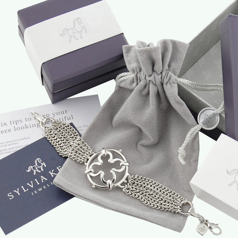 purple with white band jewellery packaging with silver bracelet