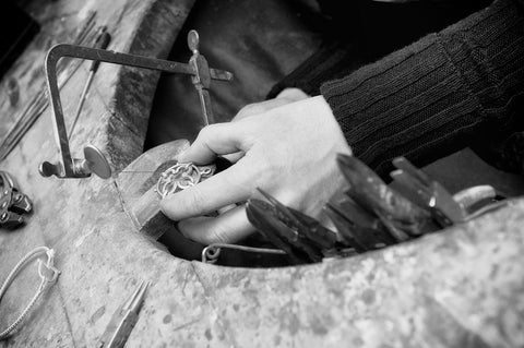image in black and white of jewellers hands making a necklace at the workbench