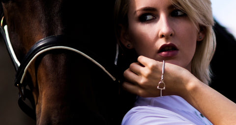 Blonde model wearing silver equestrian styled bangles next to a horse