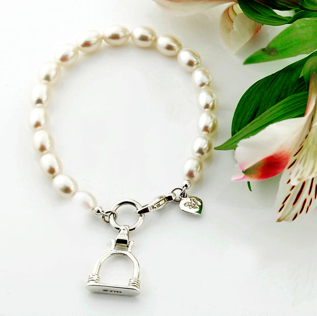 designer silver and cultured pearl bracelet with vintage stirrup charm on white background with flower.