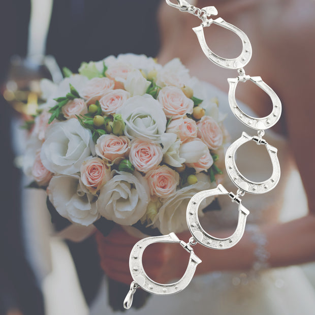 bride wearing Designer solid silver large horseshoe bracelet.