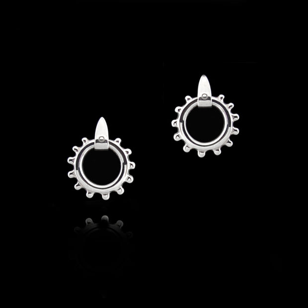 designer solid silver equestrian swivel earrings on black background.