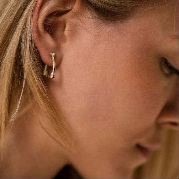 model wearing designer 9ct gold vintage stirrup inspired hoop Badminton earrings.