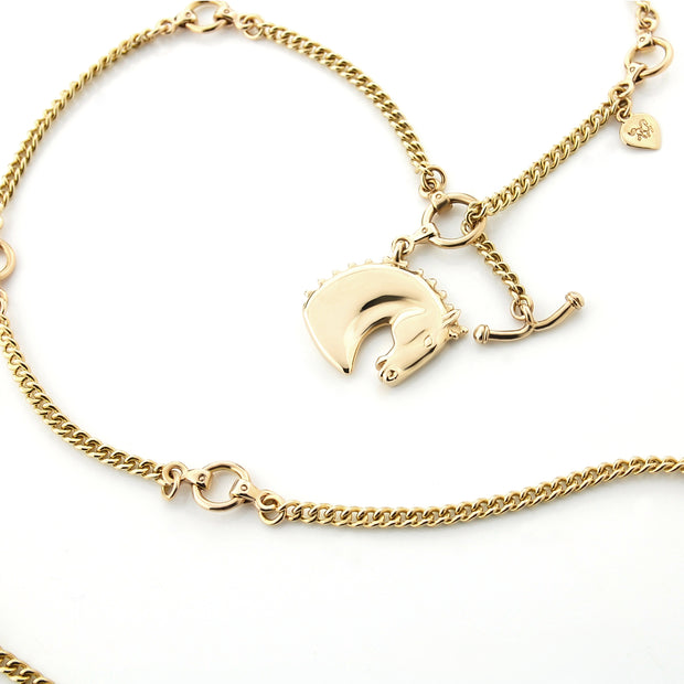 Heavy solid 9ct gold equestrian carved Horsehead necklace on white background.