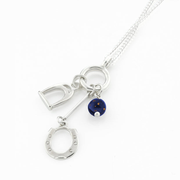 Designer solid silver horseshoe, stirrup and Lapis lazuli charm necklace on white background