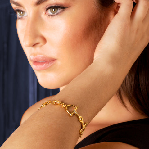 Brunette model wearing gold and diamond horsebit bracelet